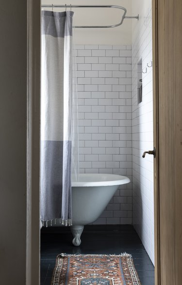 a bathroom with subway tile, a small throw rug, and a claw-foot tub with a gray and white curtain