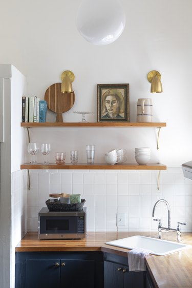 honey-colored wood shelves hold glasss, cups, and artwork