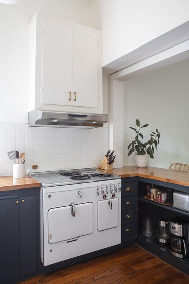 a kitchen with contemporary blue cabinets, wooden countertops, a white tile backsplash, and a vintage cast-iron stove painted white