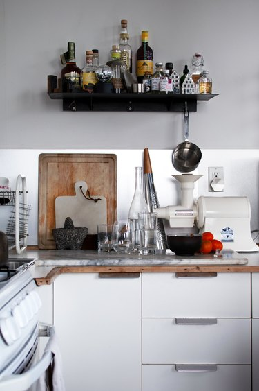 A kitchen with white cabinets, appliances and dishware