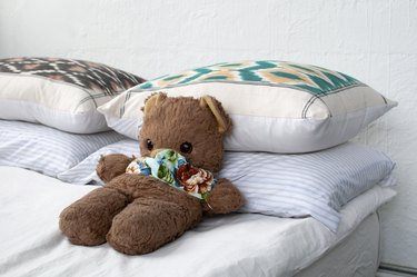 A brown teddy bear on a bed with white bedding and multicolored pillows