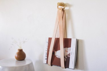 Leather strip magazine holder with wood hoop next to table with brown vase