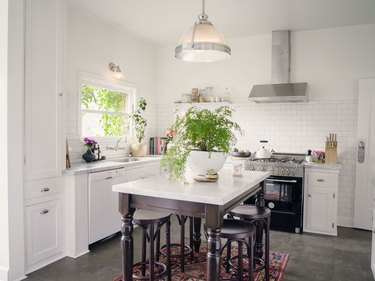 classic kitchen with white cabinets, white subway tile backsplash, marble countertops and espresso wood island with vintage rug