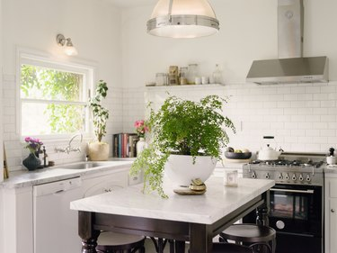classic kitchen with white cabinets, white subway tile backsplash, marble countertops and espresso wood island