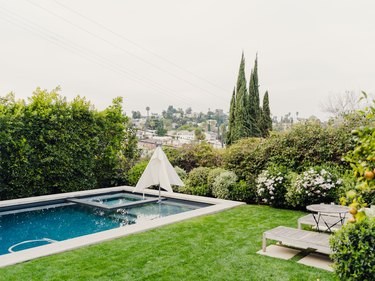 lawn next to backyard pool with pool loungers and lots of trees and greenery