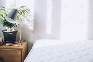 White mattress beside side table with small plant and lamp against white curtains