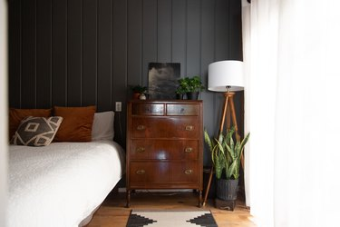Wood dresser, tripod floor lamp, and black-white southwest rug. Black wall with wainscoting. Bed with brown and gray pillows.