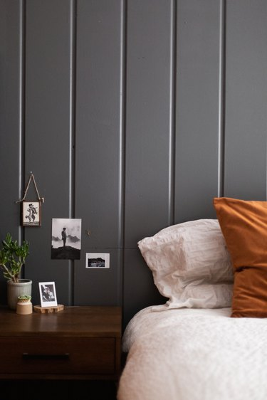 Bedroom with a gray wainscoting wall and small photos. Wood nightstand with plants and a bed with brown and neutral pillows.
