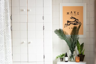 A bathroom with white tiled walls, plants, and a poster with a rabbit.