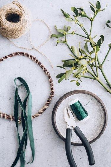 a wreath form, wire, twine, ribbon, and mistletoe