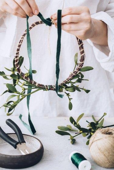 a woman wraps green ribbon around a diy mistletoe wreath in progress