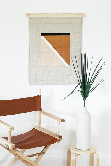 Painted quilt hanging with foldable brown chair and plant with vase on stool