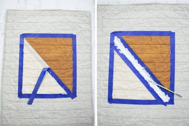 White and brown quilt with blue painters tape