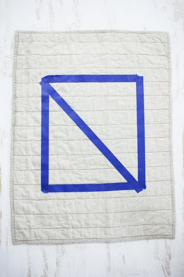 White quilted pillow with blue painters tape