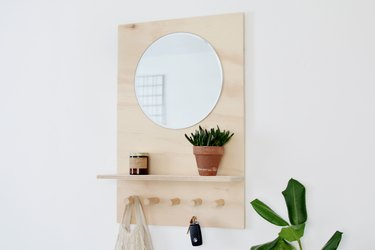 a shelving unit made from a sheet of plywood with a shelf, several thick wooden pegs, and a mirror at eye level