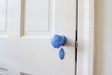 White door wit blue painter's tape on door knob and lock