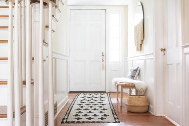 Black and white jute rug in white walled hallway with bench, basket and wood floor