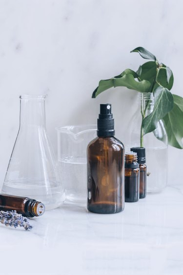 bottles of essential oil, lavender sprigs, glass beakers full of alcohol and water, and a spray bottle