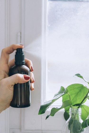 spraying the air with diy room spray