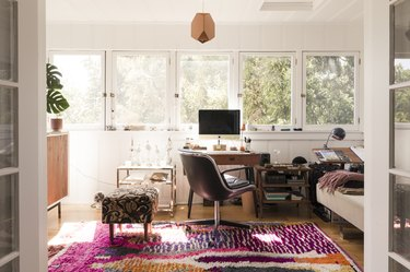 An sunny office with wood furniture, houseplants, colorful rug and geometric pendant light.