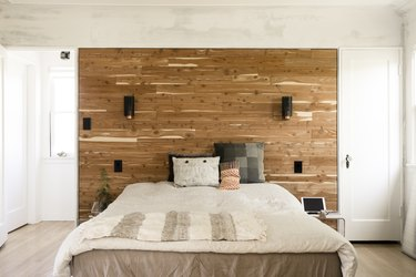 A bed with multi-colored neutral bedding and pillows. A wood accent wall behind with sconces.