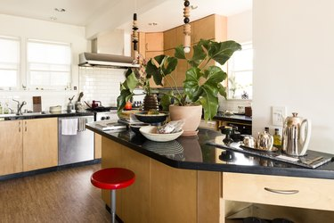 A red stool at a wood kitchen island with a black counter. Beaded pendant lights hang and a houseplant accent.