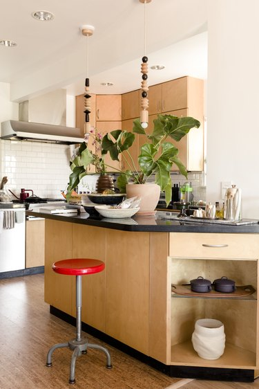 Red stool at a light wood kitchen island with black counter. Black and white dishes, a plant, and beaded pendant lights accent.