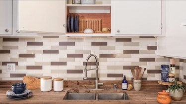 Kitchen with white-gray tile backsplash and wood countertop with white cabinets
