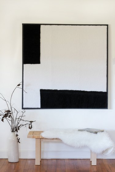 Black and white wall art over bench with fleece blanket and plant