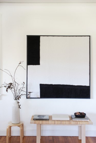 Black and white shearling wall art with bench, stool, and plant