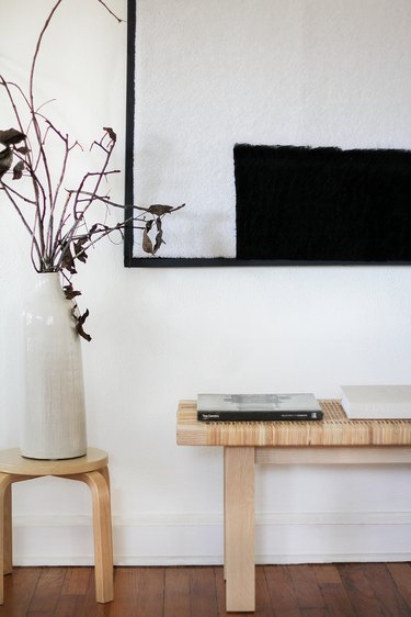 Minimalist black-white shearling wall art with bench, stool, and vase