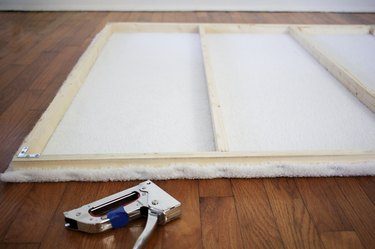 Wood frame with stapled white shearling next to staple gun