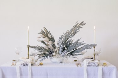 Glittery dried flowers and grass painted gray on table with dishware and candles