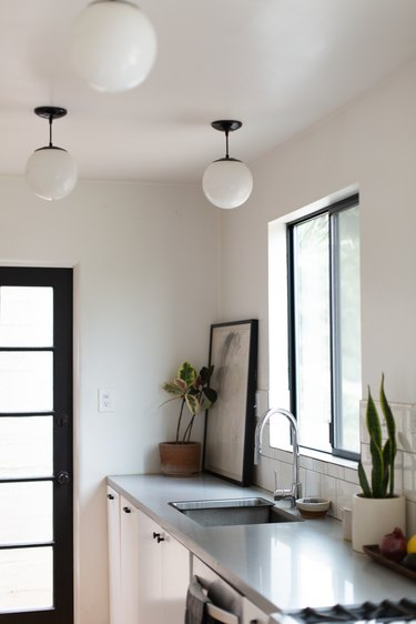 Globe pendant lights, in a kitchen with a gray counter and houseplants.