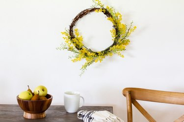 a wreath with tiny yellow flowers on a wall above a rustic wooden table