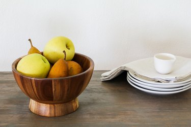 a wooden bowl full of fruit next to white saucers and napkins