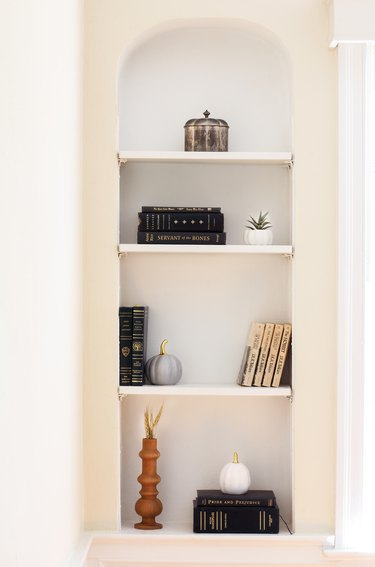a few books, a silver box, and decorative ceramic pumpkins on a set of built-in shelves