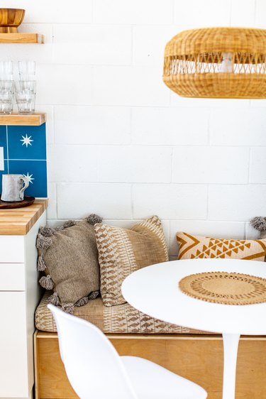 a breakfast nook with a banquette, small round table, and a wicker pendant light