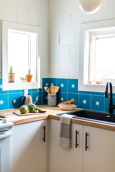 the corner of a kitchen with white walls, white cabinets, and an azure tile backsplash