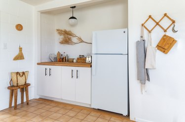 a decorative dried branch hangs on a wall next to the white refrigerator