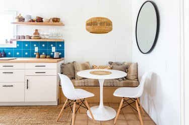 a breakfast nook with a banquette, small round table, a round mirror, and a wicker pendant light