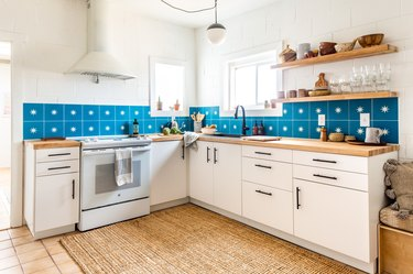 a kitchen with white cabinets, white walls, and a backsplash made of large azure tiles each with a star in the center