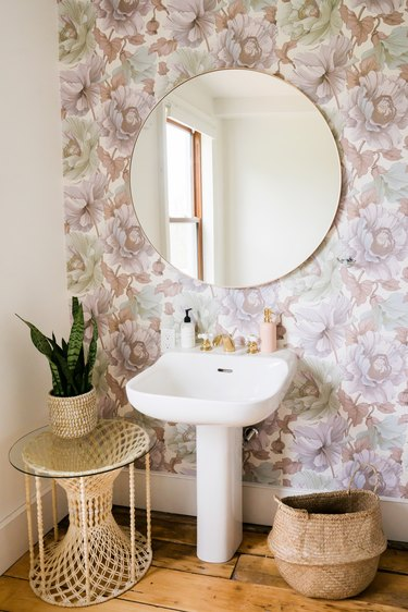 a bathroom with a pedestal sink, round mirror, and lavender-toned floral wallpaper