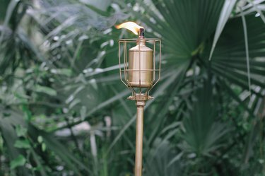 an industrial diy outdoor torch with a gold metallic finish and a lit flame