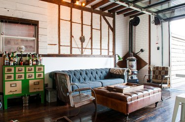 a eclectic room with a blue couch, green bar, exposed beams, and a wood-burning stove