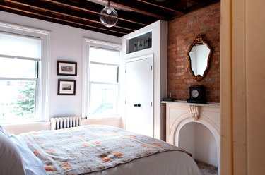 a bed with a southwestern patterned in a bedroom with exposed beams, a fireplace and one brick wall