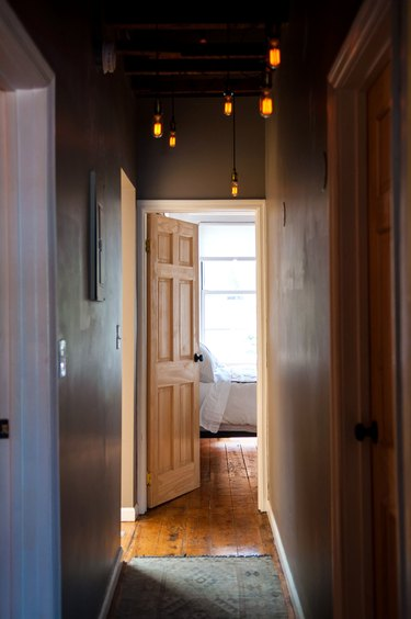 Hallway Lighting Ideas in a narrow hallway with dim pendant lights and a rustic pine floor opens into a bright bedroom
