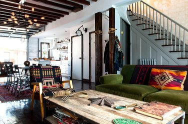 rustic industrial decor in a sitting room with a green couch, a rustic raw wood coffee table, and a staircase painted gray