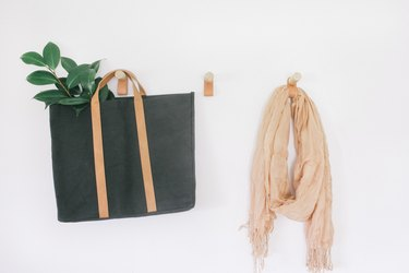 three coat hooks made from thick wooden dowels and a leather loop hanging below, with clothes and bags hanging from them