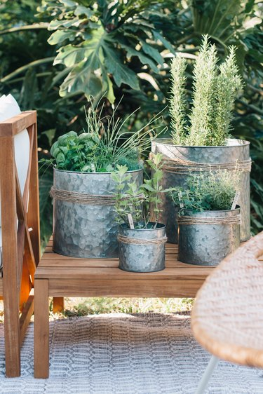 Metal planters with jute twine and plants on an outdoor wood side table